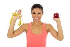 Латинская женщина спорта в одеждах фитнеса держа плодоовощ яблока и измерение связывают усмехаться тесьмой счастливый Стоковая Фотография