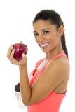 Латинская женщина спорта в одеждах фитнеса есть усмехаться плодоовощ яблока счастливый в здоровом питании Стоковое фото RF