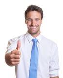 Латинский бизнесмен при голубая связь показывая большой палец руки Стоковое Фото