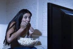 Латинское кресло софы женщины дома в живущей комнате смотря фильм ужасов телевидения страшный или триллер приостановкы Стоковые Фото