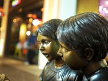 Латунная статуя мальчика и девушки Стоковое Фото