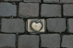 Латунная эмблема Яблока врезанная в булыжнике стоковое изображение