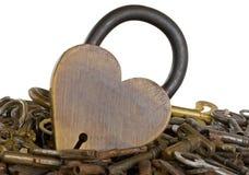 латунное изолированное сердце пользуется ключом окруженная старая замка Стоковое фото RF