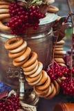 Латунный винтажный самовар, пачка бейгл, красных ягод как символ русского гостеприимства Стоковое фото RF