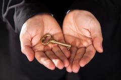 Латунный ключ в приданных форму чашки мыжских руках Стоковое Изображение