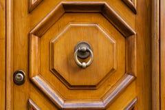 Латунный knocker двери на коричневой деревянной двери в Риме Стоковая Фотография