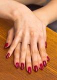Ладонь девушки с красным маникюром, на одном другое Стоковые Фотографии RF