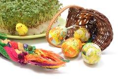 Ладонь и яичка пасхи в переворачиванных плетеной корзине и кресс-салате Стоковые Фото