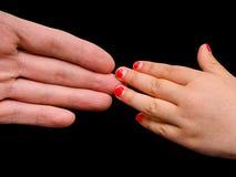 Ладонь сильной руки встречая малую руку девушки Стоковое Изображение