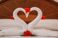 Лебеди и цветки полотенца на кровати Стоковые Изображения