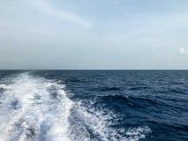Левая волна шлюпки на голубом море стоковая фотография