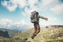 Левитация человека путешественника скача с тяжелым рюкзаком Стоковая Фотография RF