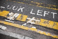 левый взгляд Дорожная разметка предосторежения, Гонконг Стоковая Фотография RF