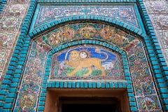 Лев с шпагой и восходящим солнцем на части мозаики крыл стену черепицей старой персидской мечети, Ирана Стоковые Изображения