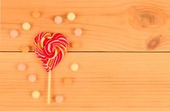 Леденец на палочке на деревянной предпосылке с помадками стоковое изображение rf