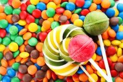 Леденцы на палочке и красочные конфеты как предпосылка стоковая фотография rf