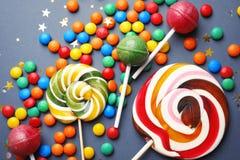Леденцы на палочке и красочные конфеты на серой предпосылке стоковое фото