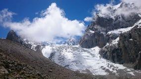 Ледник среди утесов, над им голубое небо и белое облако стоковые фотографии rf