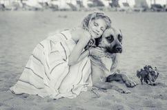 Лежать в ребенке и собаке пляжа красивом стоковая фотография
