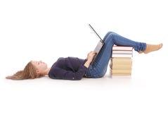 Лежать девочка-подростка студента косой на поле с компьтер-книжкой Стоковое Изображение
