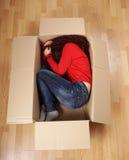 Лежать девушки завитый вверх в картонной коробке Стоковая Фотография RF