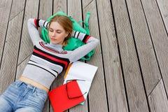 Лежать девушки отдыхая на деревянном поле в улице Стоковые Фото
