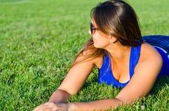 Лежать женщины ослабляя на траве Стоковое фото RF