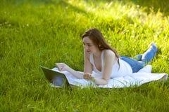 Лежать женщины ослабляя на зеленой траве Стоковые Изображения RF
