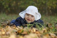 Лежать красивого младенца усмехаясь на листьях осени стоковые фотографии rf