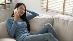 Лежать красивой молодой азиатской женщины, который усмехаясь нужно ослабить на кресле, девушке сидя на софе используя мобильный у