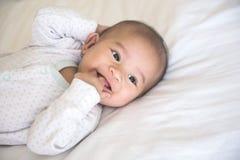 Лежать младенца усмехаясь на кровати стоковое изображение rf
