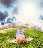 Лежать на мальчике зеленой травы беспечальном Стоковая Фотография
