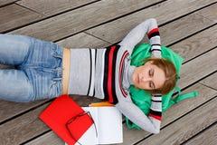 Лежать студента отдыхая на деревянном поле в улице Стоковое Изображение RF