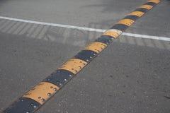 Лежачий полицейский безопасности дорожного движения на дороге асфальта стоковые изображения