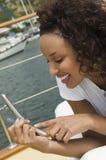 лежа мобильный телефон используя яхту женщины Стоковые Фотографии RF