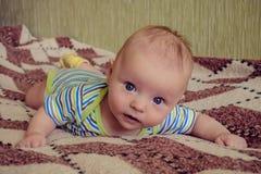 Лежа младенец смотря с любопытством Стоковое фото RF