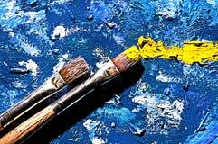 2 лежа щетки на холсте покрашенном с краской стоковая фотография