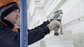 Лейборист в оранжевом unifrom полирует небольшую часть стены с небольшим молотком акции видеоматериалы