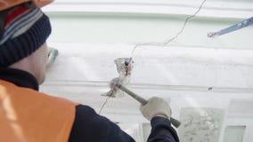 Лейборист в оранжевых работах обмундирования с небольшим молотком для того чтобы ударить часть стены фасада видеоматериал