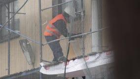 Лейборист конструкции в оранжевом равномерном жилете царапает стену с молотком на лесах видеоматериал