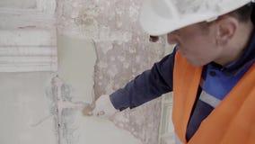 Лейборист конструкции мужской красит часть белой стены с большой кистью видеоматериал