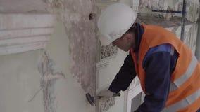 Лейборист нося оранжевый жилет и белые удары шлема с частью молотка белой стены сток-видео