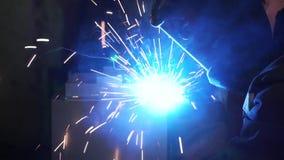Лейборист промышленного работника на структуре фабрики сваривая стальной зажим Металл заварки человека сток-видео