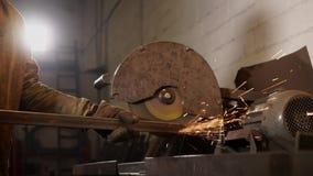 Лейборист точит край заготовки металла промышленным вращая полировщиком видеоматериал