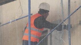 Лейборист человека в оранжевом равномерном жилете царапает стену с молотком на лесах акции видеоматериалы