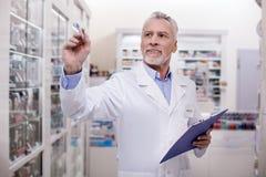 Лекарства внимательного мужского аптекаря расчетливые Стоковые Изображения