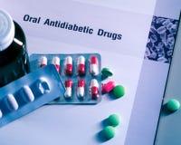 Лекарства диабета в пакетах и и бутылка медицины помещенная на учебнике Зеленые таблетки и розов-белые пилюльки капсулы Сахарный  стоковое изображение rf