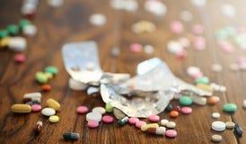 Лекарства и монетки в стеклянном опарнике на деревянном поле Карманные сбережения Стоковые Фото