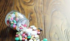 Лекарства и монетки в стеклянном опарнике на деревянном поле Карманные сбережения Стоковое фото RF