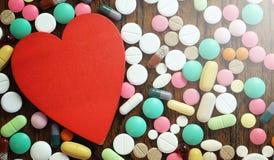 Лекарства и монетки в стеклянном опарнике на деревянном поле Карманные сбережения Стоковая Фотография RF